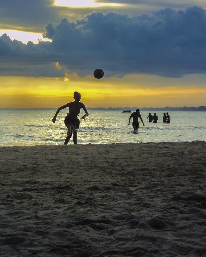 Folk som spelar fotboll på stranden arkivfoto