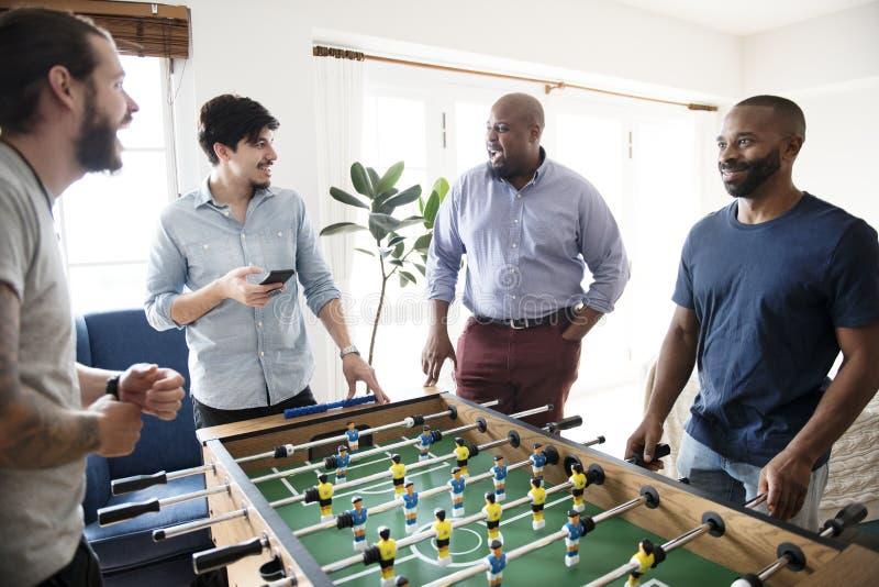 Folk som spelar tabellfotboll tillsammans fotografering för bildbyråer