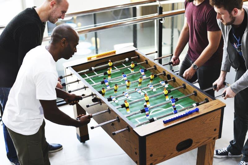 Folk som spelar tycka om rekreation Le för lek för Foosball tabellfotboll arkivbild