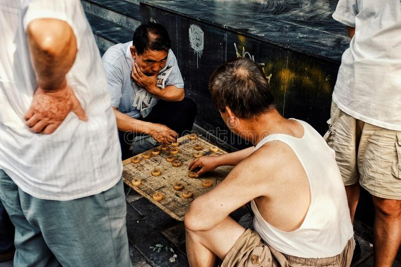Folk som spelar typisk xiangqikinesschack på gatan i en traditionell kinesisk stadshutong royaltyfri foto