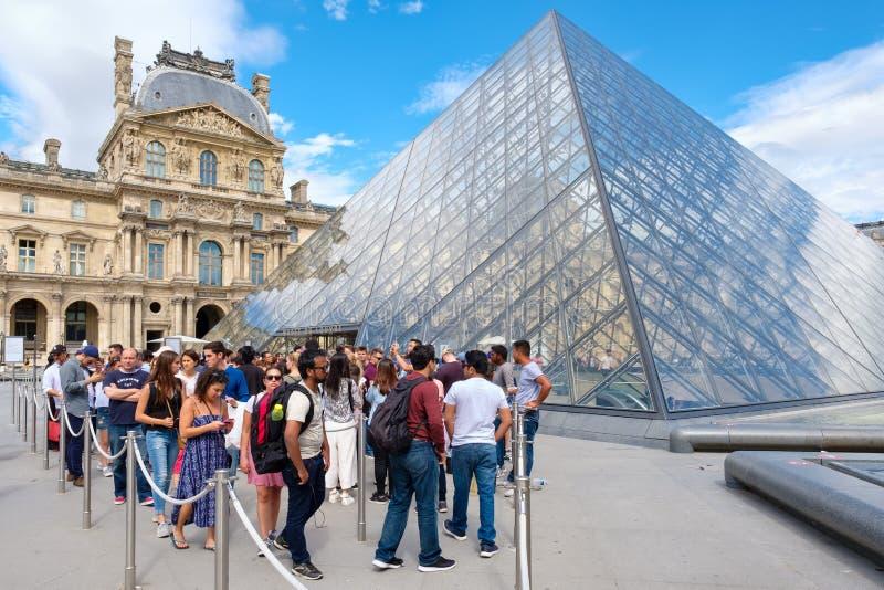 Folk som står i linjen som väntar för att skriva in Louvremuseet i Paris arkivbild