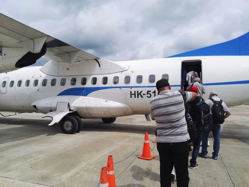 Folk som stiger ombord en liten propellernivå från landningsbanan av en tropisk flygplats arkivbild