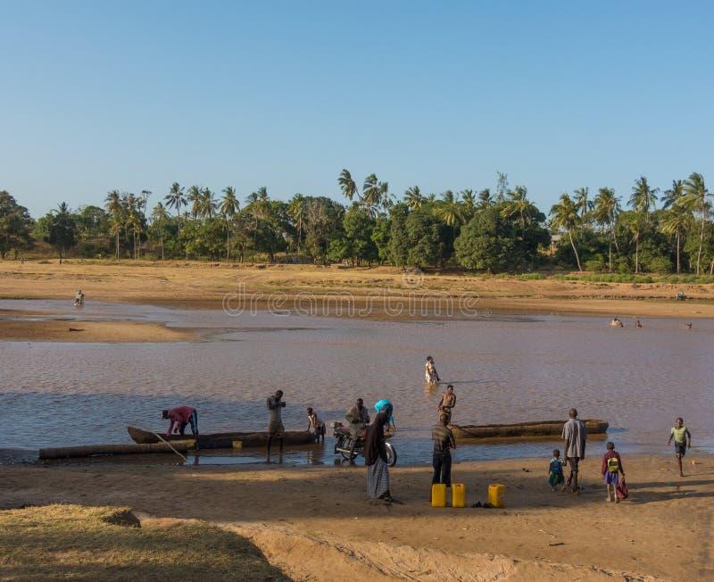 Folk som stiger ombord kanoter på den Galana floden, Kenya royaltyfria bilder