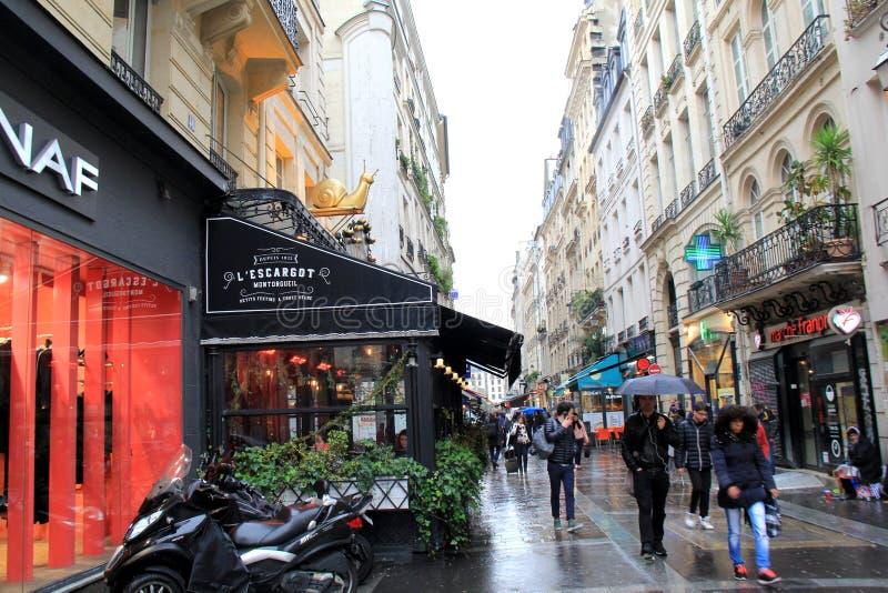 Folk som strosar till och med regnet, hållande paraplyer, nära berömd restaurang, L'Escargot, Paris, Frankrike, 2016 royaltyfria bilder