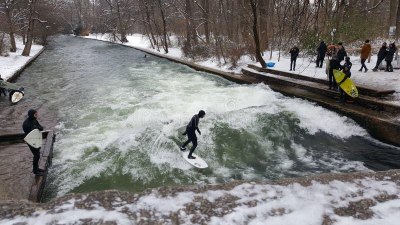 Folk som surfar i vinter på den Eisbach anseendevågen i Munich, Tyskland royaltyfri foto