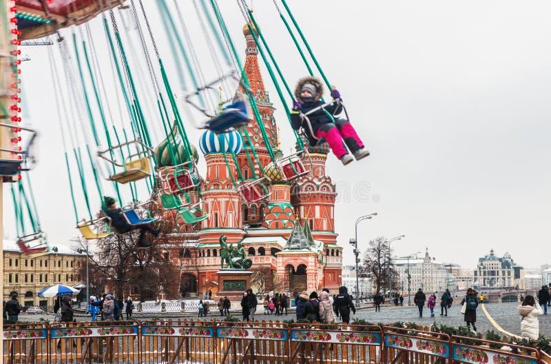 folk som svänger på karusellen på bakgrunden av Pokroven royaltyfri fotografi