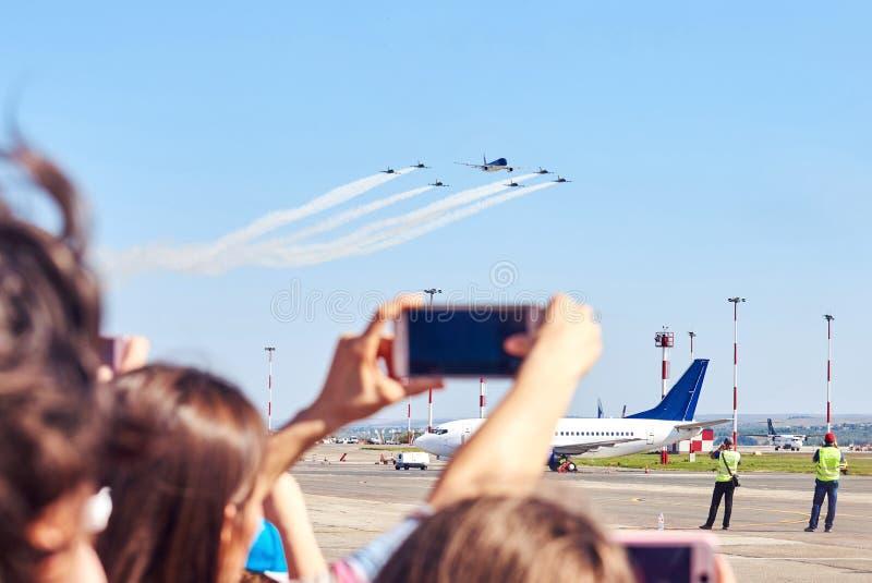 Folk som tar foto av flygplanet med deras smartphones royaltyfria bilder