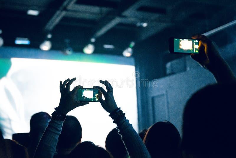 Folk som tar fotografier med den smarta telefonen under en musikkonsert Person som fångar en video på en mobiltelefon på en musik royaltyfri fotografi