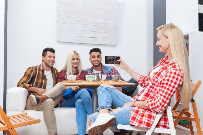 Folk som tar selfievänner bilder som dricker coffee shop med telefonen för håll för män för lopp för blandning för baristasammant royaltyfri bild