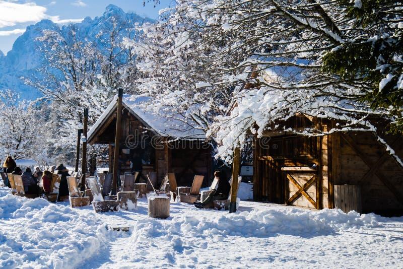 Folk som tycker om att solbada i terrass för ` s för restaurang för snöig vinterlandskap utomhus- trä royaltyfria bilder