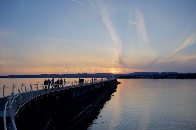 Folk som tycker om den härliga solnedgången, medan gå på vågbrytaren på Odgen punkt, Victoria F. KR. royaltyfria bilder