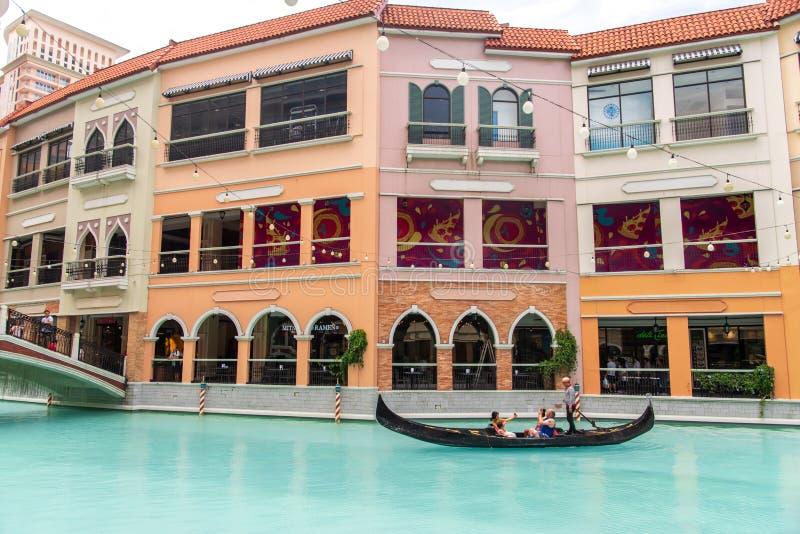 Folk, som tycker om gondoler i gallerian Venedig f?r den storslagna kanalen, tunnelbanan Manila, Filippinerna, Maj 4, 2019 arkivfoto