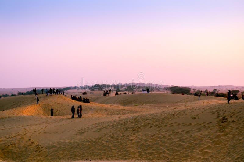 Folk som tycker om solnedgången på sanddyn fotografering för bildbyråer