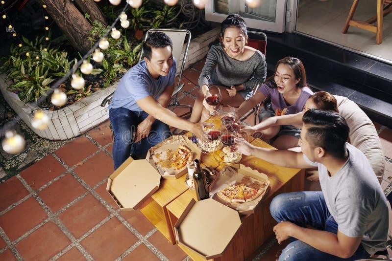 Folk som tycker om vin och mat i trädgård arkivbilder