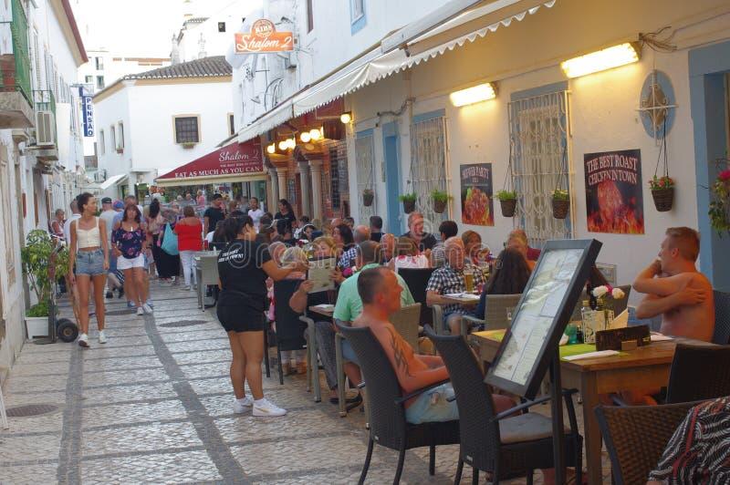 Folk som ut äter middag på utomhus- restauranger royaltyfri foto