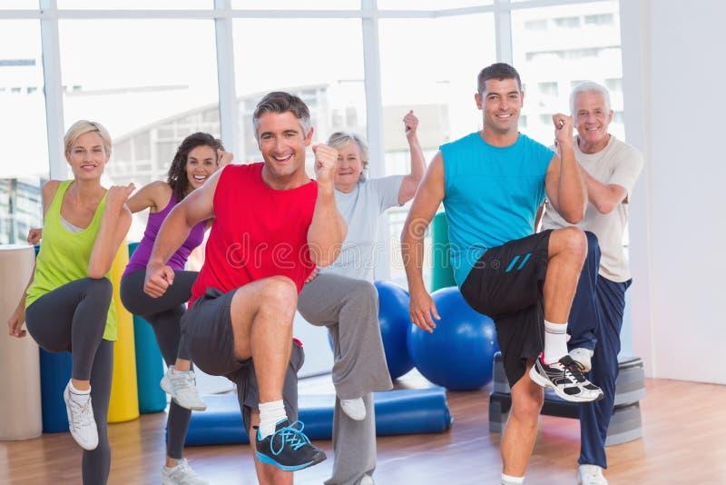 Folk som utför aerobicsövning i idrottshallgrupp arkivbild
