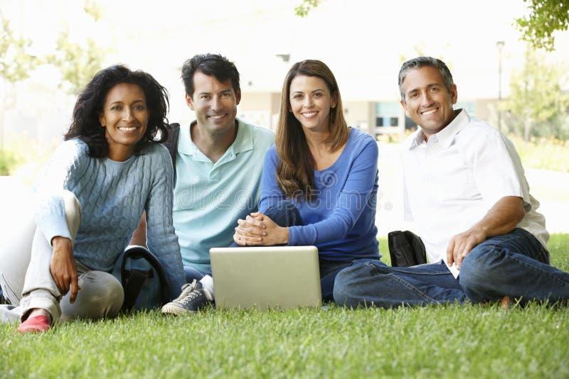 Folk som utomhus använder bärbara datorn arkivfoto