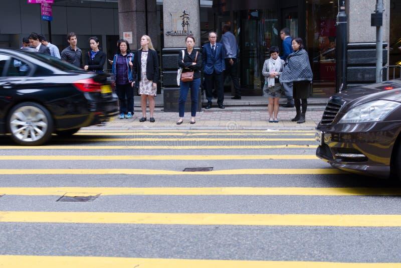 Folk som väntar för att korsa gatan, övergångsställe på den upptagna vägen, daglig trafik för stad arkivbild