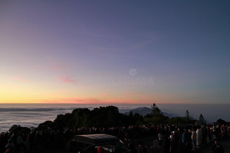 Folk som väntar för att se solen stiga överst av ett berg royaltyfria foton