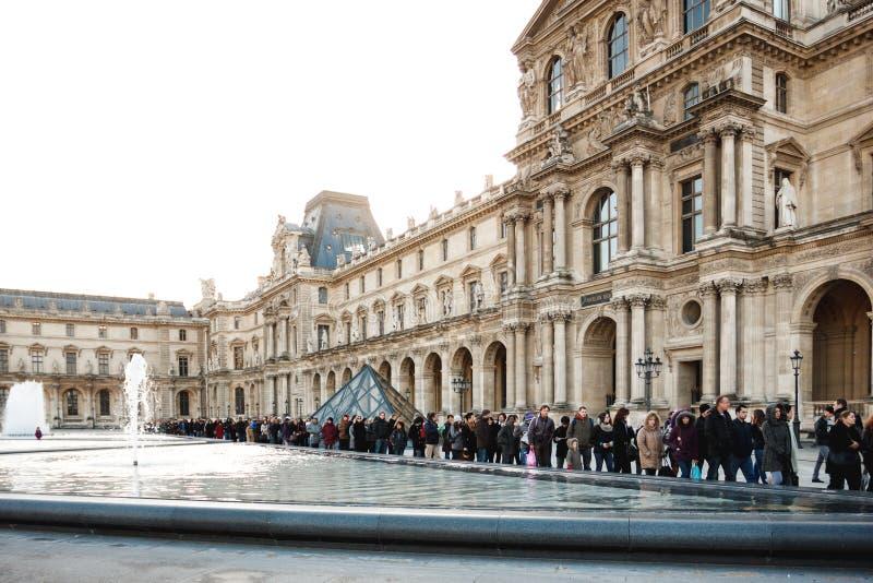 Folk som väntar i en kö för att besöka Louvremuseet royaltyfri bild