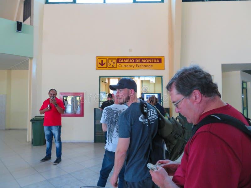 Folk som väntar i linje på den Holguin flygplatsen för att utbyta deras valuta royaltyfria bilder