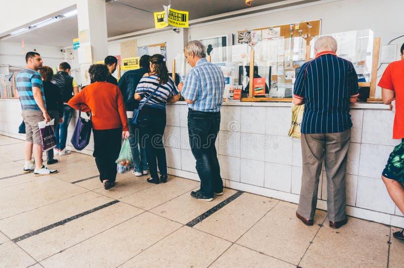 Folk som väntar i linjen på stolpen - kontor arkivfoto