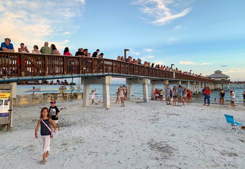 Folk som väntar på solen för att ställa in på fortet Myers Beach arkivbilder