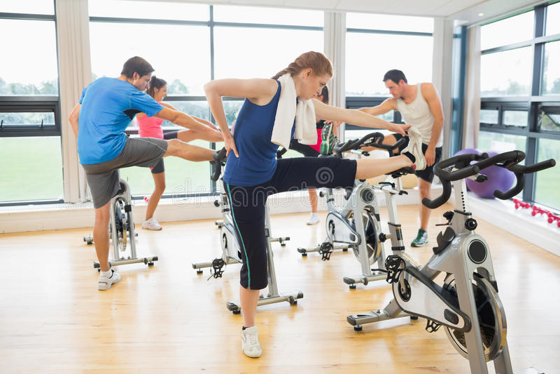 Folk som värmer upp med motionscykeler i snurrgrupp arkivbilder