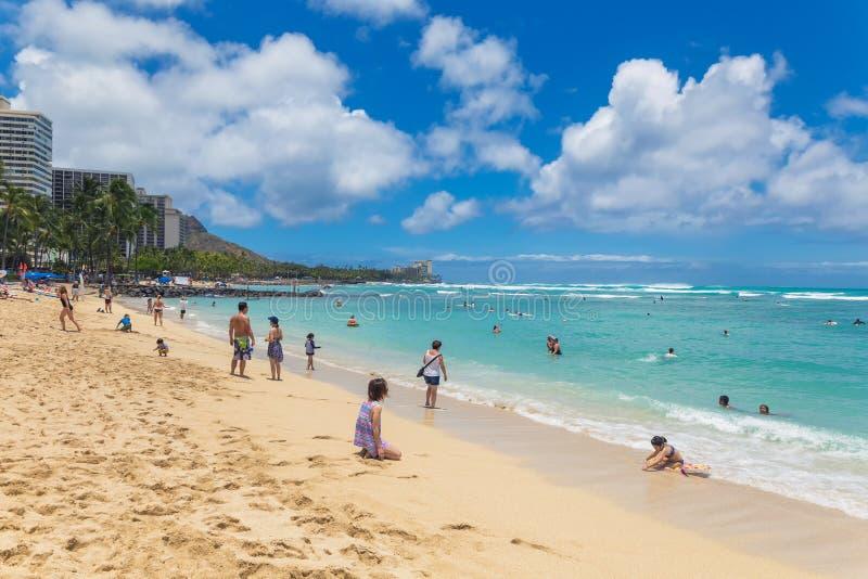 Folk som vilar och solbadar på den berömda Waikiki stranden på den Oahu ön royaltyfri fotografi