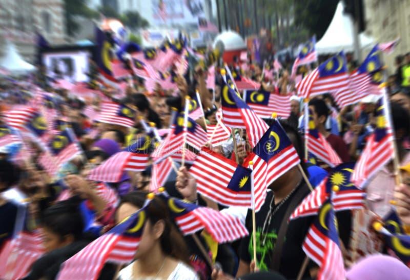 Folk som vinkar malaysiska flaggor arkivbilder
