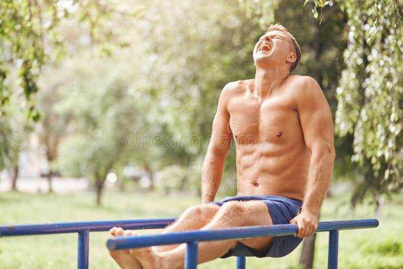 Folk sport, motivationbegrepp Den stiliga muskulösa mannen gör exersices som är utomhus- tidigt i morgon, bär kortslutningar, arb royaltyfri fotografi