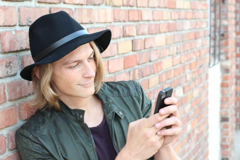 Folk, teknologi, fritid och livsstil - ung man med det smsande meddelandet för smartphone på stadsgatan fotografering för bildbyråer
