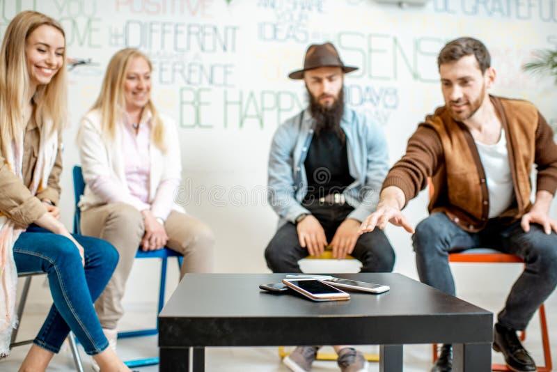 Folk under den psykologiska terapin med telefoner i kontoret royaltyfri fotografi