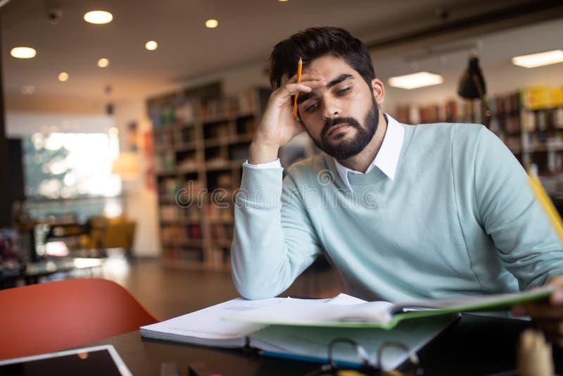 Folk, utbildning, studera, examina och skolabegrepp - trött student som lär i arkiv arkivfoto