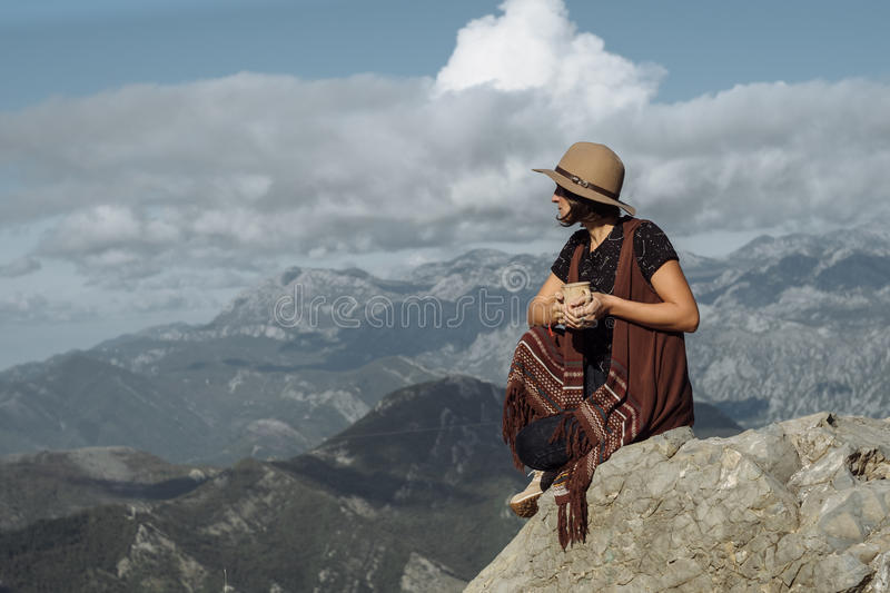 Folk woman in Hat drinking tea in nature fall mountain landscape royalty free stock photos
