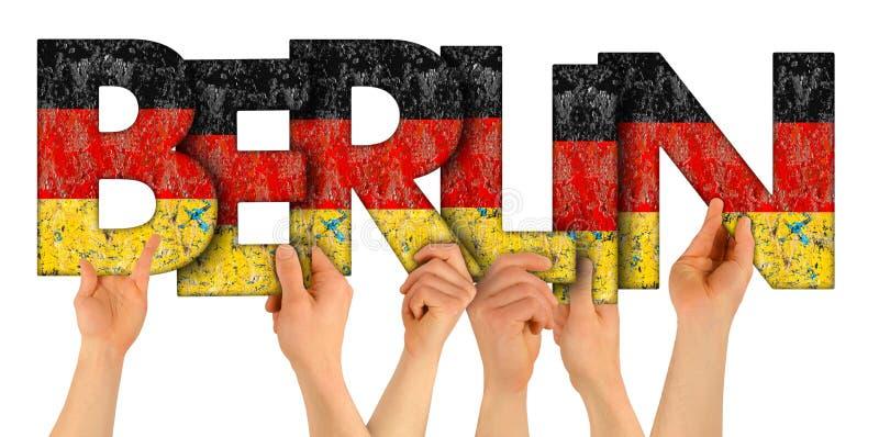 Folkarmh?nder som rymmer upp tr?bokstavsbokst?ver som bildar ordBerlin huvudstaden av Tyskland i tyska nationsflaggaf?rger royaltyfri bild