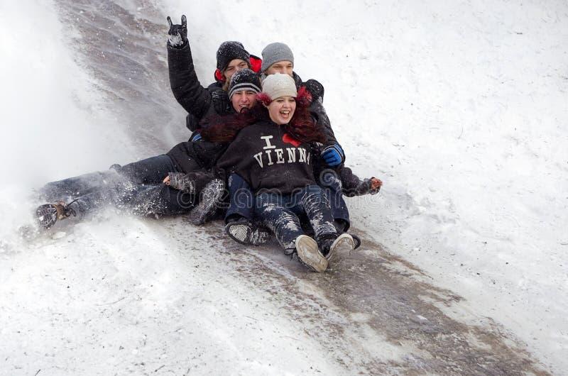 Folkbarn rider på vintersnön som sledding från kullar Vinter som spelar, gyckel, snö arkivfoton