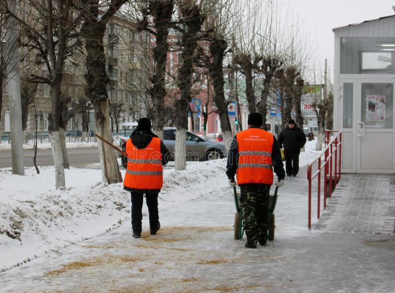 Folkdörrvaktarbetare strilar hala gator i staden med sand i vinter mot is arkivfoto