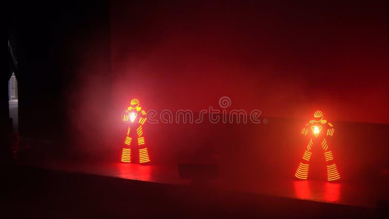 Folkdans i ledde dräkter Två dansare på etapp utför robotdans i ledde dräkter med ljusa ljus dans arkivfoto