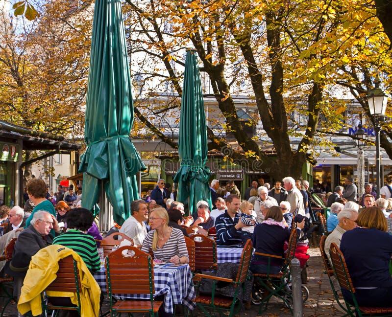 Folkdrink utanför på den Viktualien Markt ölträdgården i Munich G arkivbilder
