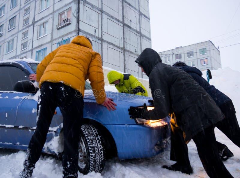 Folket är driftigt ut ur en snödriva som en bil klibbade i snön royaltyfri foto