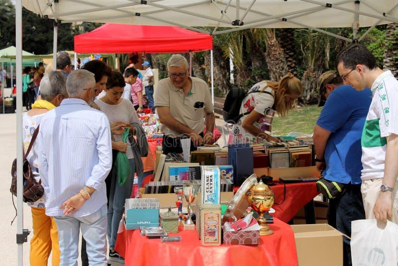 Folket är hålla ögonen på och sälja saker i antikvitet- och bokställning för en gata arkivbild