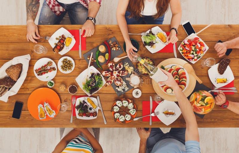 Folket äter måldrinkalkohol på det festliga tabellmatställepartiet royaltyfri foto