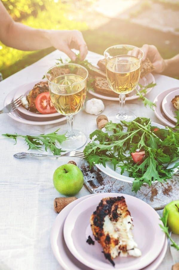 Folket äter på tabellen i trädgården Matställe på solnedgången med vin, den grillade fisken, nya grönsaker och örter Skjuten lodl royaltyfri foto
