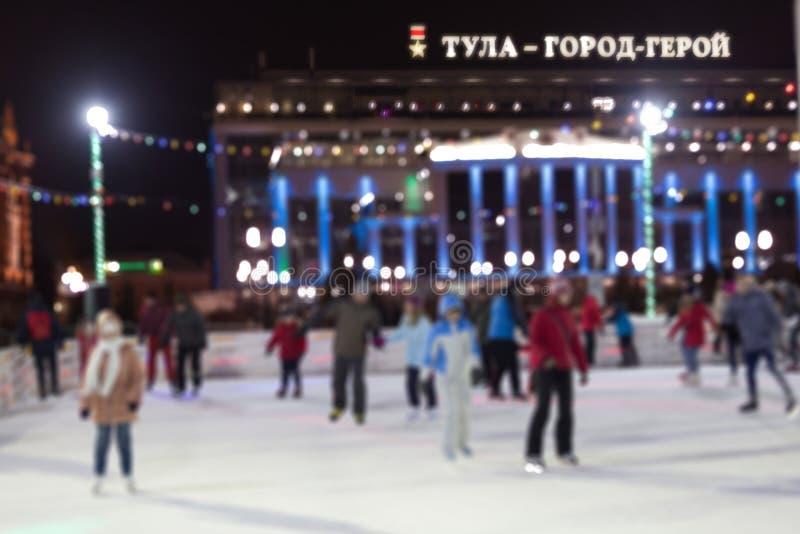 Folket åker skridskor i aftonen på en åka skridskor isbana för stad suddighet textur royaltyfri fotografi