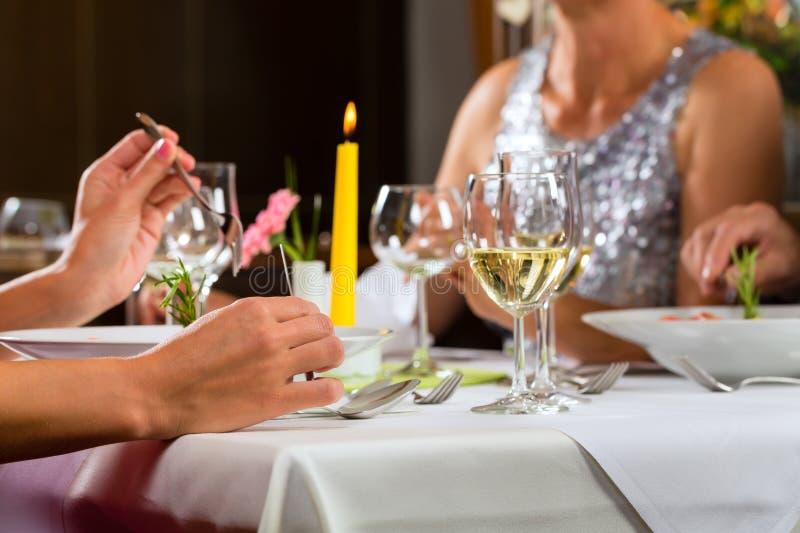Folket bötfäller att äta middag i elegant restaurang royaltyfri bild