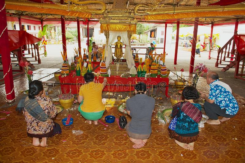 Folket ber framme av den berömda forntida guld- Pra smällstatyn under Lao New Year beröm i Luang Prabang, Laos arkivbild