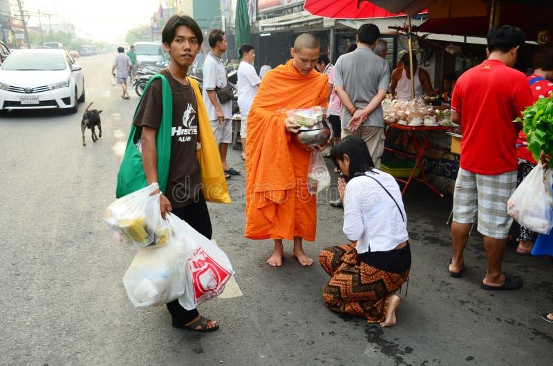 Folket ber med munken och sätter matofferings till den buddistiska allmosabunken royaltyfri bild