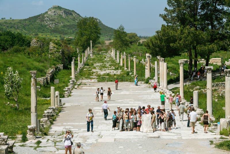 Folket besöker promenad nära amfiteater i Ephesus Ancie arkivfoton