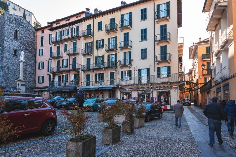 Folket besöker smala gator för raditionalitalienare med härlig arkitektur av städer runt om Como sjön royaltyfri bild